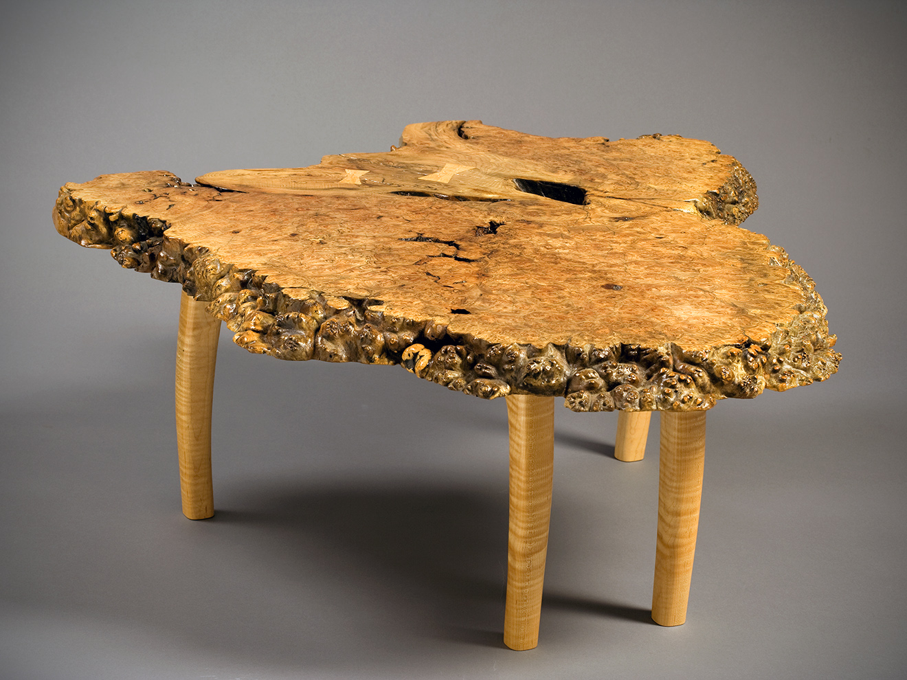 """Big Leaf Maple Burl Coffee Table Big Leaf Maple Burl top with Birds-Eye Maple Butterfly inlays. Tiger Maple sculpted legs and apron. Mortise and tenon construction. 16.5""""h × 38""""w × 42""""d"""