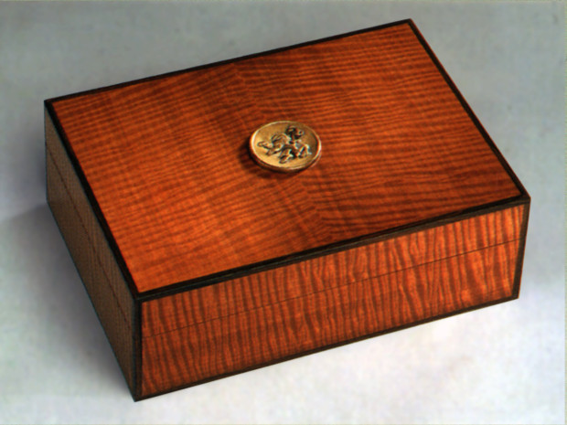 "Fiddleback Makore Humidor Book-matched Fiddleback Makore veneer, solid Mahogany, Ebony inlay. Casting made from original hand carving. 4 ½""h × 9""w × 12 ¾""d"