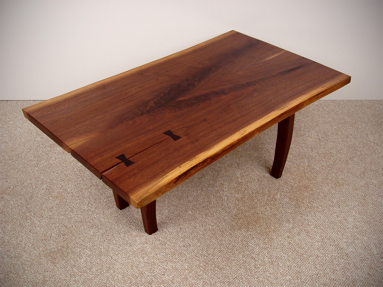 "Walnut Coffee Table Book matched Black Walnut flitches with Ebony inlaid butterflies. The base uses mortise and tenon, lap joint construction and hand-carved tapered legs. 16""h × 38""w × 20""d"