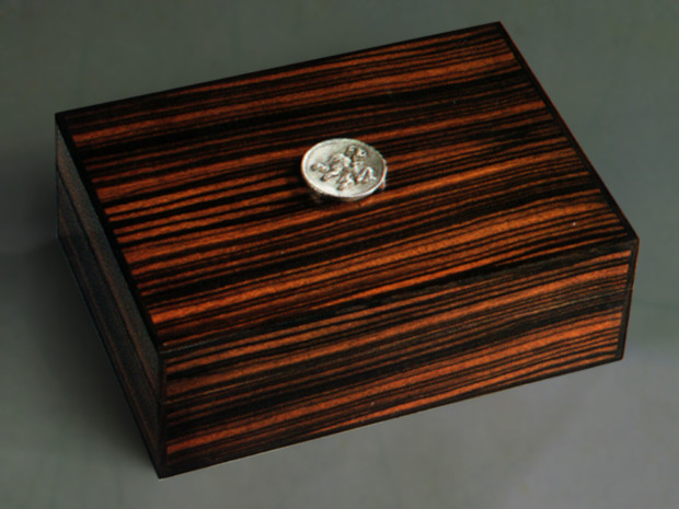 "Macassar Ebony Humidor Book matched Macassar Ebony with ebony inlay. Pewter casting of original carved design by Tom Lederer. Mitre-spline construction and Spanish Cedar lining. 4.5""h × 12/75"" × 9""w"