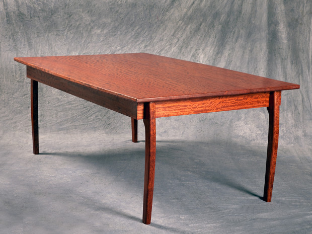 """Waterfall Bubinga Dining Table Solid Bubinga dining table with tapered top, hand sculpted legs and a varnish finish. 30""""h × 73""""l × 48""""w"""
